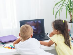Boy and girl sit in front of laptop with pencils and notebooks on desk