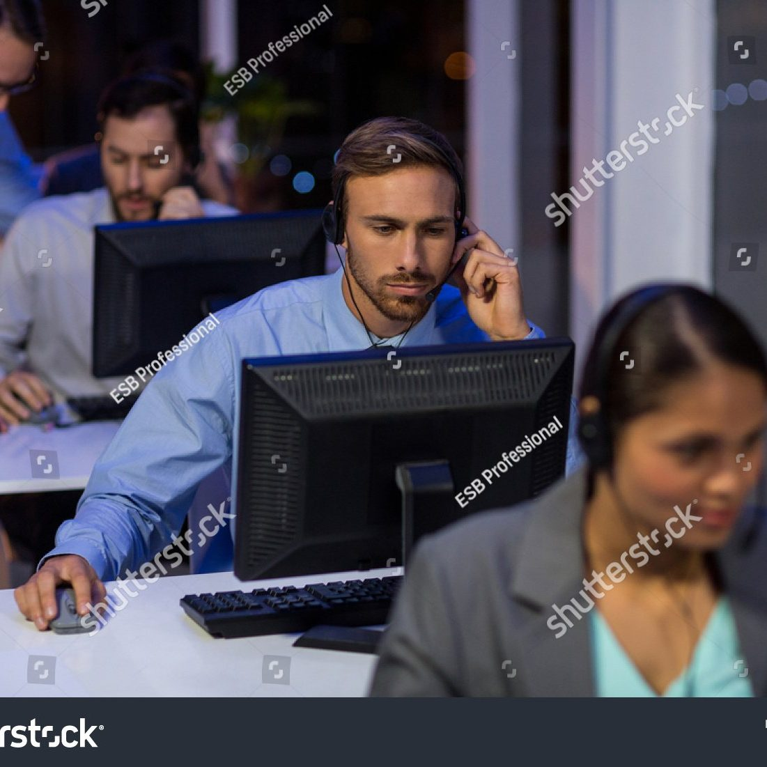 stock-photo-businessman-with-headsets-using-computer-in-office-at-night-491362219