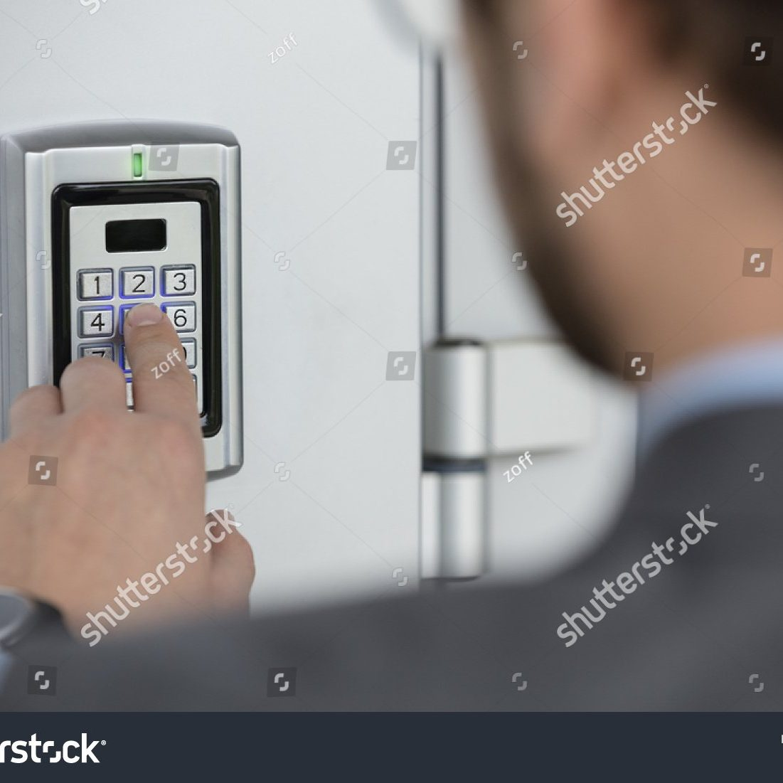 stock-photo-close-up-of-businessman-hand-entering-security-system-code-406405123